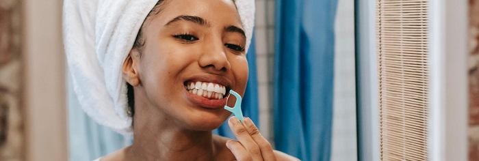 Kvinna som använder tandtråd